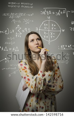 Thoughtful girl holding pen and documents and solving equation. - stock photo