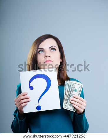 thoughtful girl in a blue shirt on a gray background holding a question mark and money