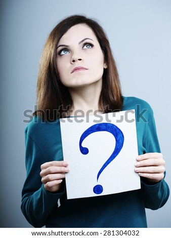 thoughtful girl in a blue t-shirt holding a question mark