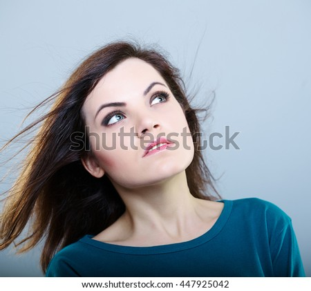 thoughtful girl in a blue t-shirt with flying hair looks upward, on a gray background - stock photo