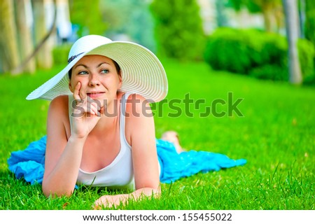 thoughtful girl lies on a green lawn in a white hat - stock photo