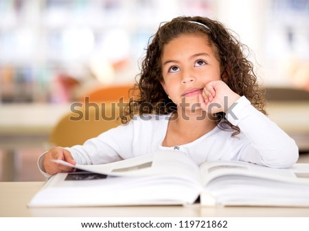 Thoughtful girl reading a book and using her imagination - stock photo