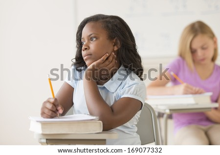 Thoughtful girl with hand on chin looking away while sitting at classroom desk - stock photo
