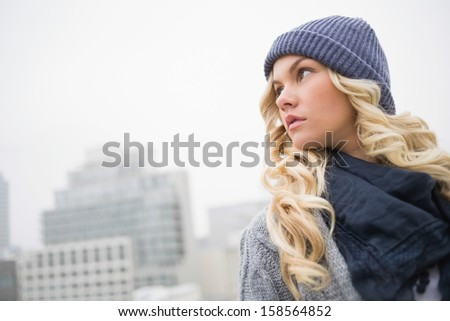 Thoughtful gorgeous blonde posing outdoors on urban background - stock photo