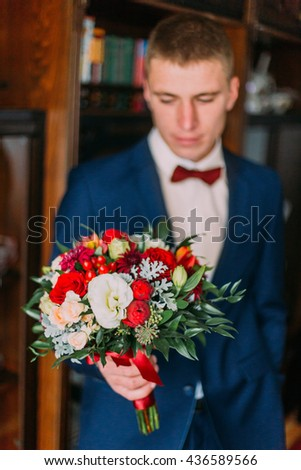 Thoughtful groom holding wedding bouquet before ceremony indoors