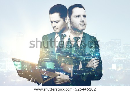 Thoughtful handsome businessman using laptop on abstract night city background. Employment concept. Double exposure