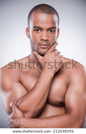 Thoughtful handsome. Portrait of young African man holding hand on chin and looking at camera while standing against black background - stock photo