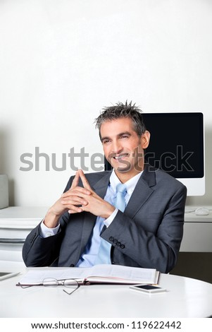 Thoughtful happy businessman sitting at desk in office - stock photo