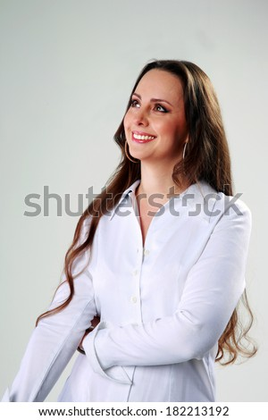 Thoughtful happy woman standing and looking up over gray background - stock photo