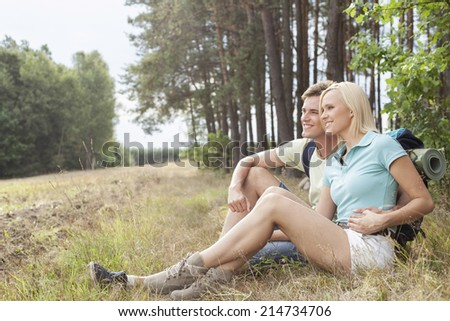 Thoughtful hiking couple looking away while relaxing in forest - stock photo