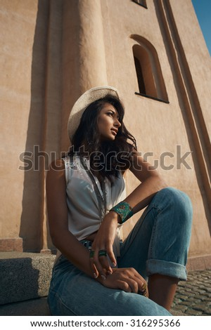thoughtful indian lady in jeans, white shirt and white hat against ancient building. She is in harsh morning light. She is positive and playful. Building looks like church or eastern temple - stock photo