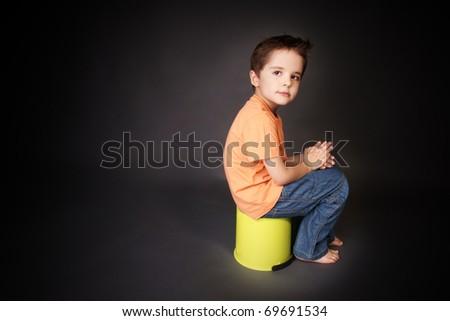 Thoughtful little beautiful boy with attentive look, studio shot - stock photo