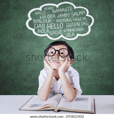 Thoughtful little girl studying multi language with a book and imagine foreign words - stock photo