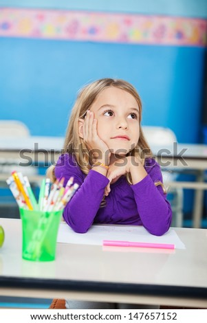 Thoughtful little girl with hand on chin sitting at desk in kindergarten - stock photo