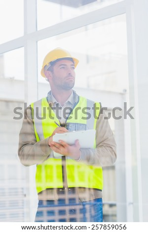 Thoughtful male architect in reflective clothing writing on clipboard at office - stock photo