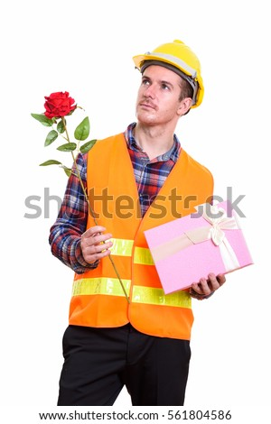 Thoughtful man construction worker holding red rose and gift box ready for Valentine's day