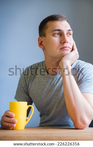 Thoughtful man having coffee in kitchen at home in the morning - stock photo