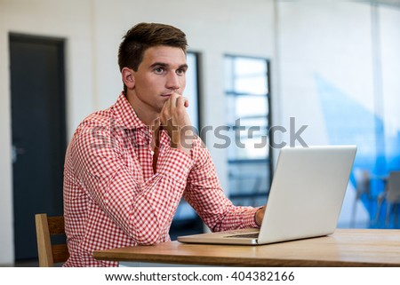 Thoughtful man in office sitting at desk using laptop - stock photo