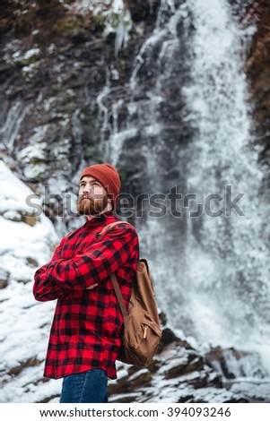 Thoughtful man with backpack and arms folded standing near a waterfall outdoors and looking away - stock photo