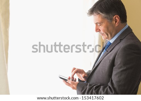Thoughtful mature businessman texting on his mobile phone on white background - stock photo