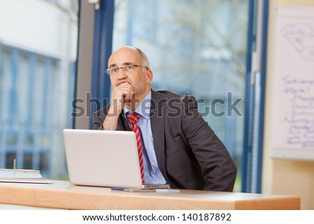 Thoughtful mature businessman with hand on chin looking away at office desk - stock photo