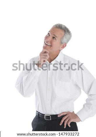 Thoughtful mature businessman with hand on chin looking up against white background