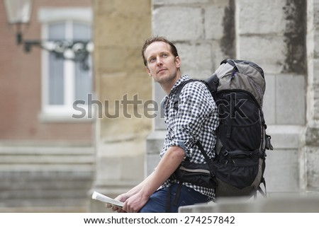 Thoughtful mid adult tourist with backpack looking away in city - stock photo