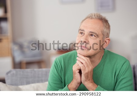 Thoughtful middle-aged man staring into space with a serious expression and his chin resting on his hands, close up view in his living room - stock photo