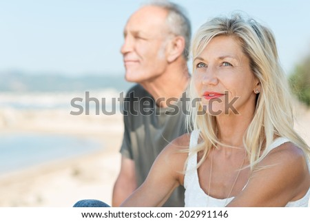 Thoughtful middle-aged woman relaxing at the sea sitting alongside her husband looking up into the sky with a contemplative expression - stock photo