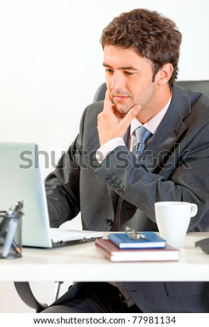 Thoughtful modern businessman sitting at office desk and working on laptop