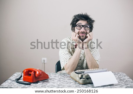 Thoughtful nerd writer in office - stock photo