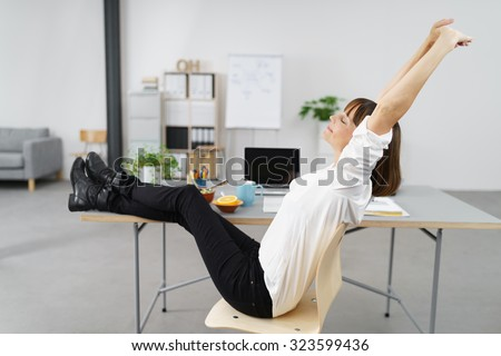 Thoughtful Office Woman Stretching her Body While Sitting on her Chair with Legs on the Desk. - stock photo