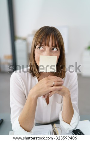 Thoughtful Office Woman with an Empty Sticky Note on Face, Sitting at her Table and Looking Up. - stock photo