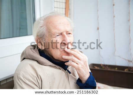 thoughtful old man smoking a cigarette - stock photo