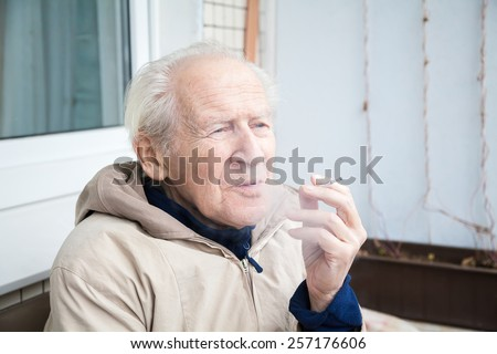 thoughtful old man with a cigarette, he is exhaling smoke - stock photo