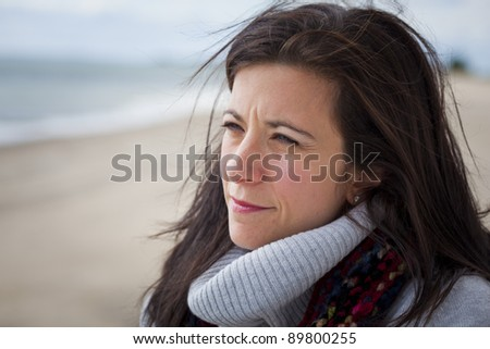 Thoughtful pretty woman at beach looking out to sea - stock photo
