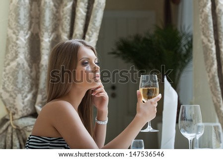 Thoughtful pretty woman posing with glass of wine - stock photo