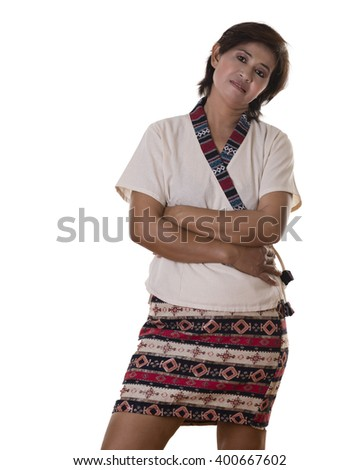 Thoughtful pretty woman with dark hair and wearing colorful skirt leans head to one side