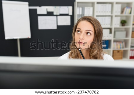 Thoughtful Pretty Young Office Girl at her Worktable, Holding Pen While Looking Up. - stock photo