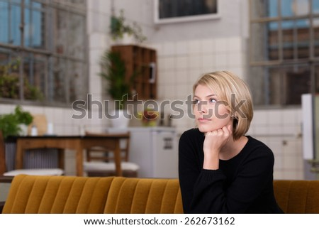 Thoughtful Pretty Young Woman with Short Blond Hair, Wearing Black Long Sleeve Shirt, Sitting on the Couch at the Living Room. - stock photo