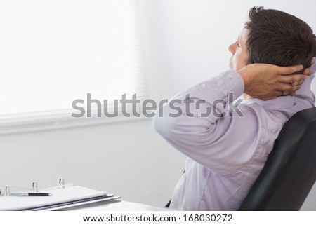 Thoughtful relaxed businessman sitting with hands behind head in the office