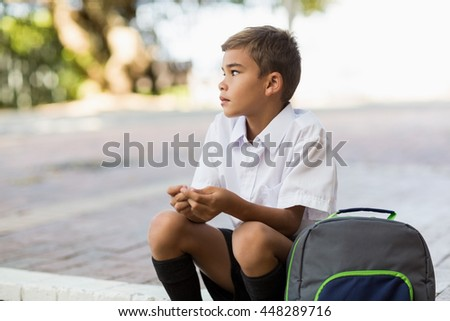 Thoughtful schoolboy sitting alone in campus at school - stock photo