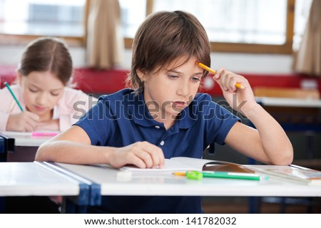 Thoughtful schoolboy sitting at desk with girl studying in background - stock photo