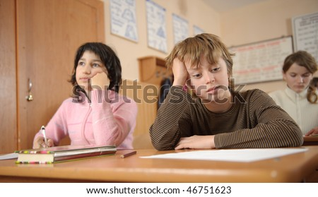 Thoughtful schoolchildren with head on theirs hands - stock photo