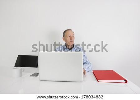 Thoughtful senior businessman using laptop at office desk - stock photo