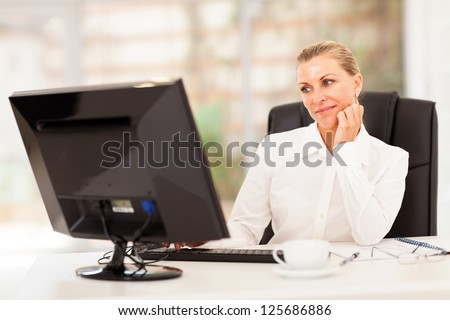 thoughtful senior businesswoman in front of computer - stock photo