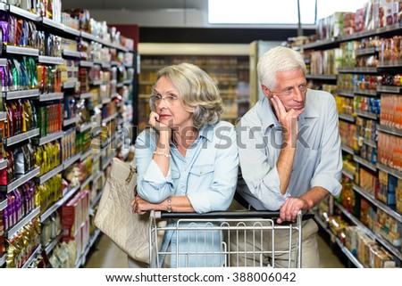 Thoughtful senior couple with cart at the supermarket