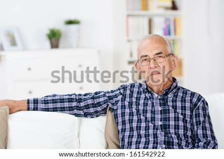 Thoughtful senior man at home sitting in a chair in the living room looking at the camera with a serious expression - stock photo