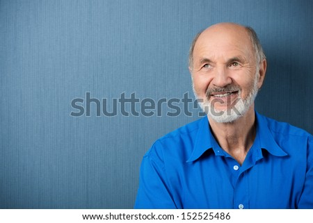 Thoughtful senior man daydreaming looking up into the air with a smile as he stands against a blank green chalkboard with copyspace - stock photo