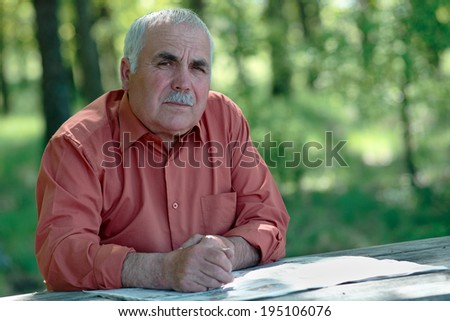 Thoughtful senior man looking at the camera with a speculative expression as he pauses in his reading of the newspaper while sitting outdoors in a wooded leafy green garden - stock photo